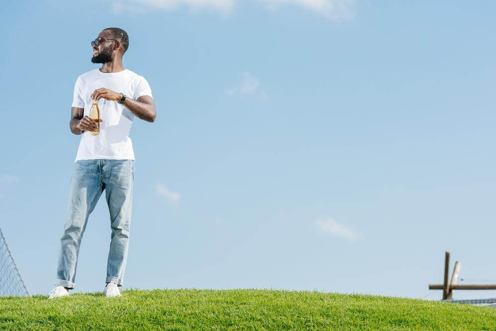 A guy is standing outside with a drink in hand.