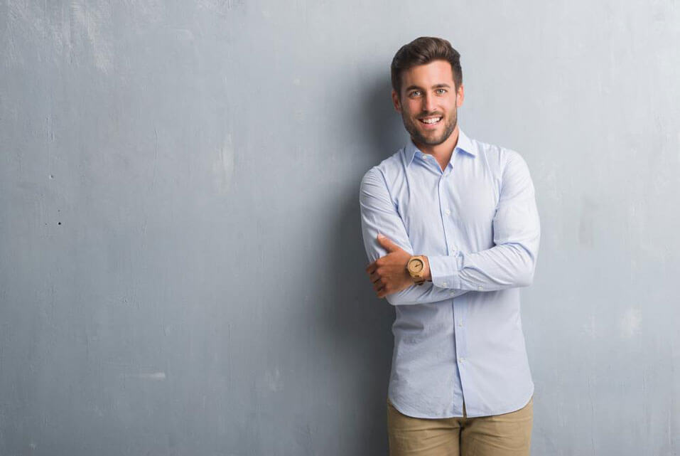 A guy is smiling against a grey background