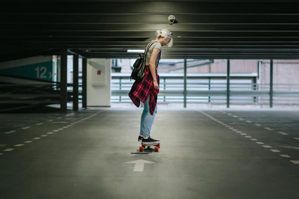 A girl with a flannel wrapped around her waist is skateboarding.