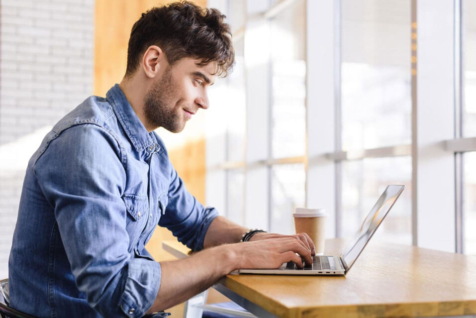A guy is smiling while staring at his laptop.
