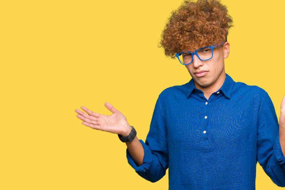 Confused man standing with yellow background