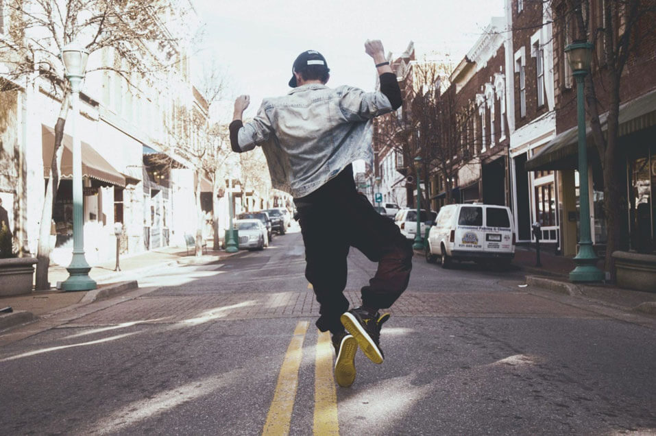 guy jumping in middle of street