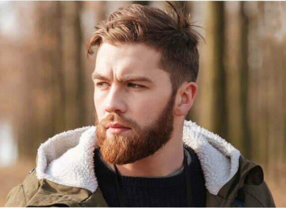 Man with a beard in a green sweatshrit