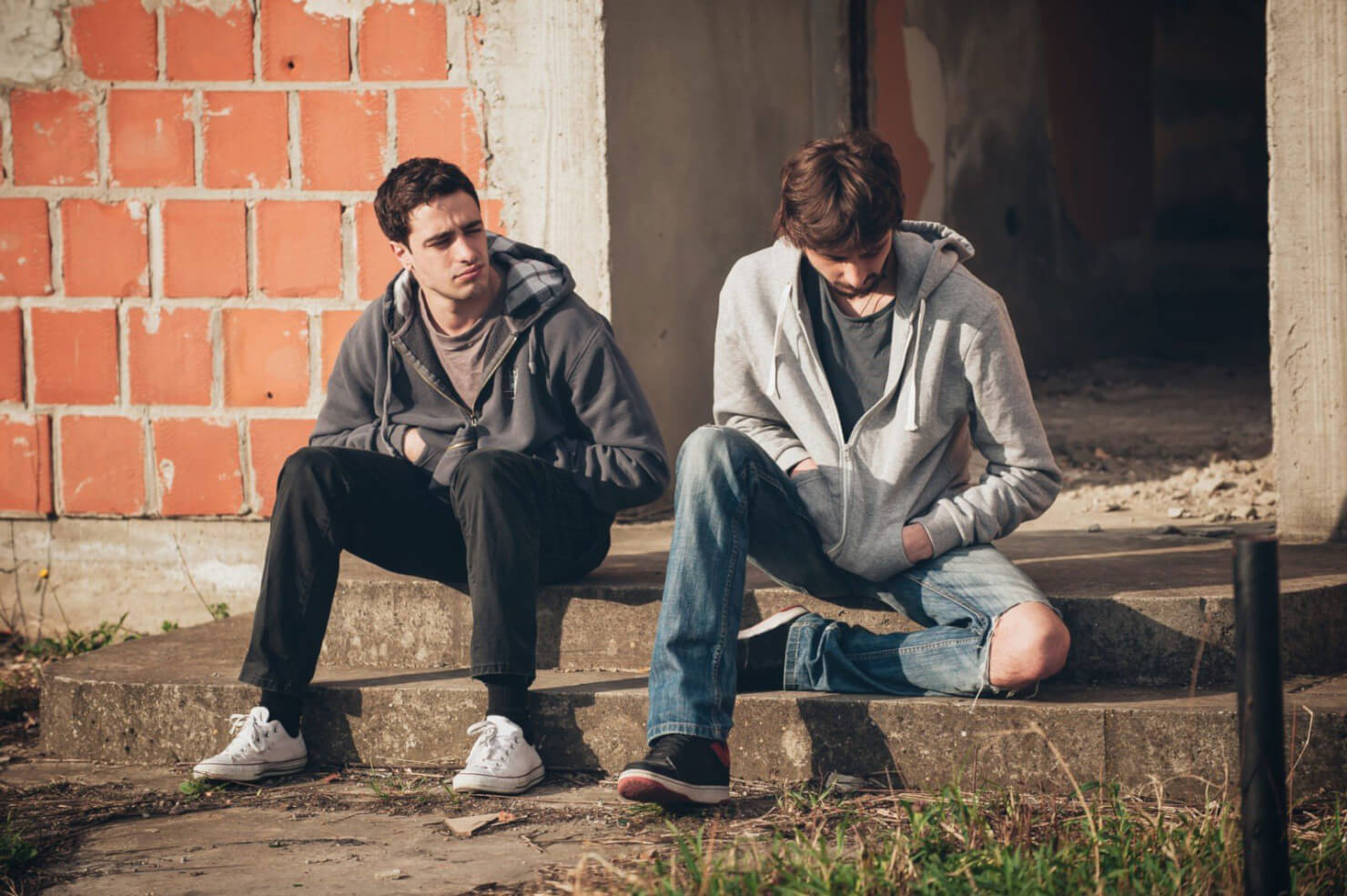 Two men sitting against a brick wall