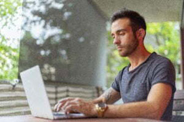 A young man is sitting outside using his laptop.