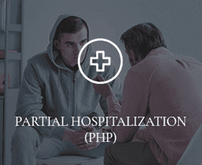 """A counselor is speaking to a Prosperity Haven patient, with the words """"PARTIAL HOSPITALIZATION"""" overtop of the photo."""