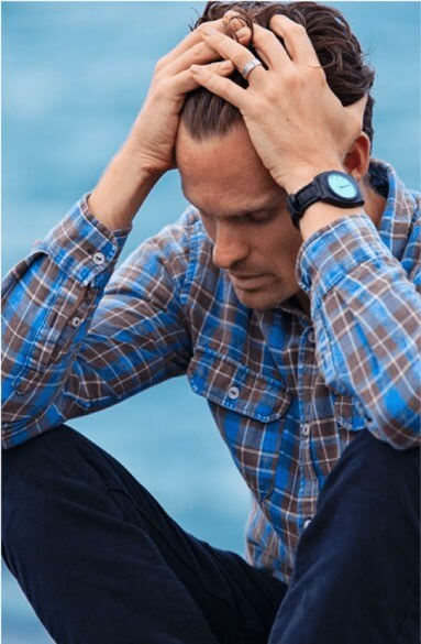 A man is holding his head and appears to be experiencing a crisis.