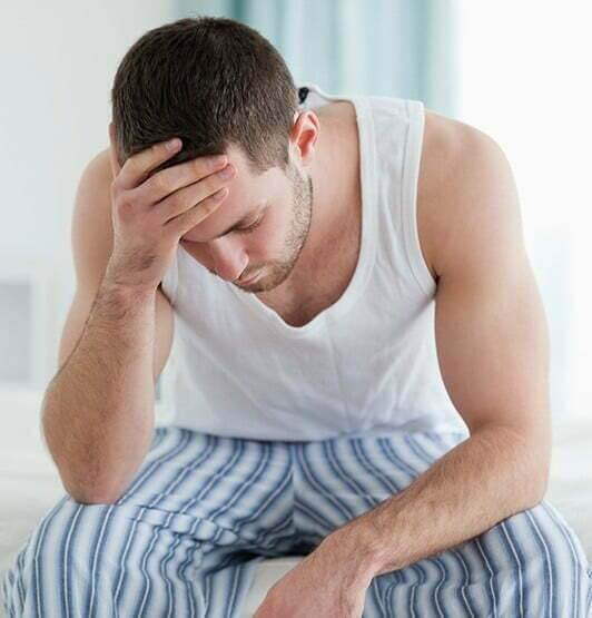 A man in a tank top is drowsy and hunched over.