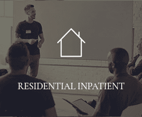 """A man is speaking to a group of people, with the words """"RESIDENTIAL INPATIENT"""" overtop of the photo."""