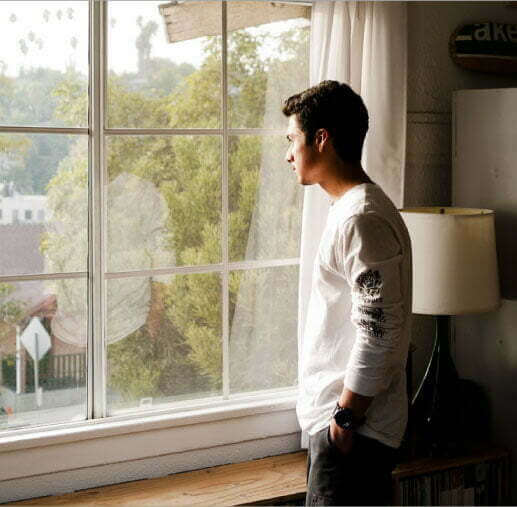 A young guy is standing while looking out a window.