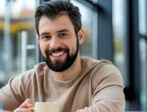 Man smiling in a tan sweatshirt