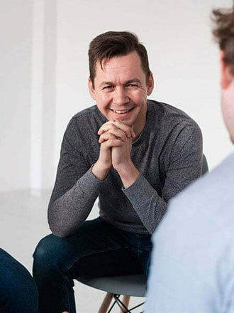 Man smiling with his hands folded